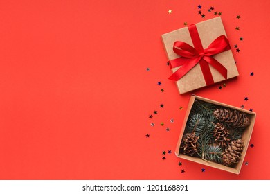 Natural cones in open gift box on red background