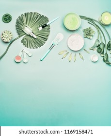 Natural cosmetic background. Tools and accessories for home facial skin care with flowers and green tropical leaves, top view, flat lay. Serum,  face mask and candle on turquoise background.