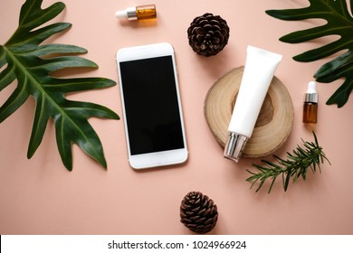 natural cosmetic cream , serum, skincare blank bottle packaging with leaves herb, wood . bio organic product.beauty and spa concept. online shopping with mobile phone and credit card.