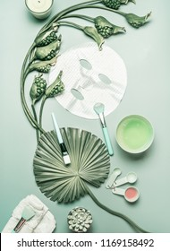 Natural cosmetic flat lay. Facial sheet mask for home facial skin care with flowers and green tropical leaves, top view, flat lay. Serum and essence  on turquoise background. Beauty concept