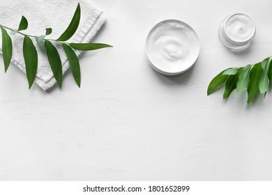 Crème d'hygiène cosmétique naturelle avec serviette et plantes vertes sur fond blanc, vue de dessus, espace pour copie. Dermatologie, concept de soin de la peau organique avec feuilles vertes.