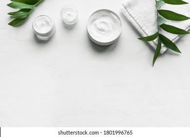Crème d'hygiène cosmétique naturelle avec serviette et plantes vertes sur fond blanc, vue de dessus, espace pour copie. Dermatologie, concept de soin de la peau organique avec feuilles vertes, bannière.