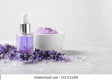 Natural cosmetic oil, bath salt, scrub and lavender flowers on grey marble table, space for text