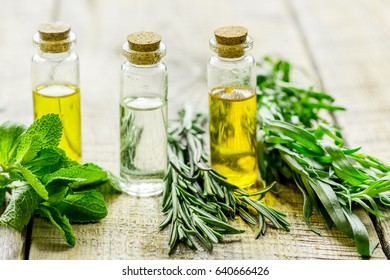 natural cosmetic oil with fresh rosemary and mint on light wooden table background