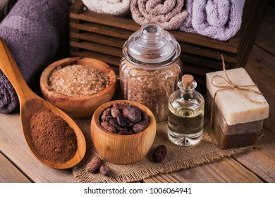 Natural cosmetic oil, sea salt and natural handmade soap with cocoa beans on rustic wooden background. Healthy skin care. SPA concept.