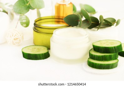 Natural cosmetic products, skincare cream in jar, yogurt, essential oil, mix with green cucumber slices