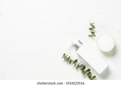 Natural cosmetic, skincare product for face and body care. Eucalyptus cosmetic, spa product at white table.