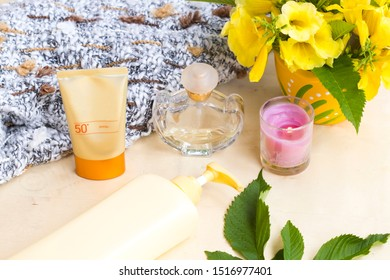 natural cosmetic sunscreen spf50 for skin face with body lotion health care body skin ,perfume and knitting wool scarf ,candle ,flowers of lifestyle woman in winter season  arrangement flat lay style