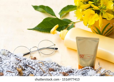 natural cosmetic sunscreen spf50 for skin face with body lotion health care body skin and knitting wool scarf ,flowers of lifestyle woman in winter season  arrangement flat lay style on wooden