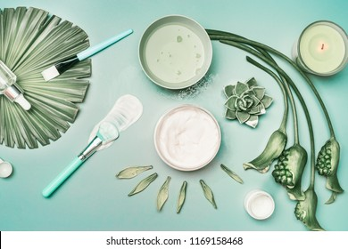 Natural cosmetic and tools for home facial skin care with flowers and green tropical leaves, top view, flat lay. Serum,  face mask and candle on turquoise background. Beauty concept