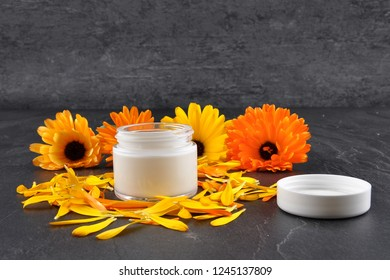 Natural cosmetics, common marigold and petals on shale