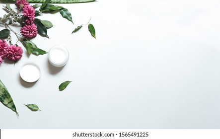 Natural cosmetics. Composition with body care products, wisp and green leaf and purple flowers over white background, top view,  FLAT LAY.