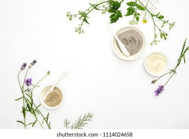 Natural cosmetics concept with various kinds of cosmetic clays ready for spa treatment decorated with healing summer herbs, flat lay composition with blank space for a text