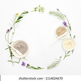Natural cosmetics concept with various kinds of cosmetic clays ready for spa treatment decorated with healing summer herbs, flat lay wreath composition with blank space for a text