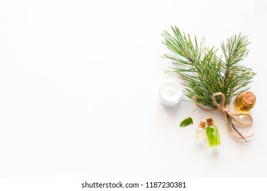 natural cosmetics and a fur-tree branch on a white background with copy space