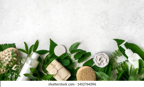 Natural cosmetics and green leaves on white stone background, copy space. Natural organic skincare, bio research and healthy lifestyle concept.