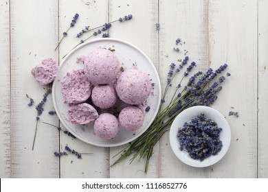 Natural cosmetics. Handmade lavender bath bombs and lavender flowers on white wooden planks, top view