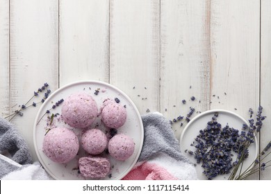 Natural cosmetics. Handmade lavender bath bombs, lavender flowers and towel on white wooden planks, top view