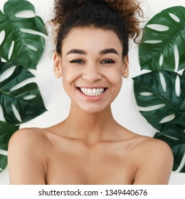 Natural cosmetics. Happy woman against tropical leaves, crop