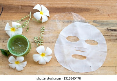 natural cosmetics herbal aroma hyaluronic nets sheet mask ,soothing gel  from herbal health care for skin face essence face mask with flower frangipani arrangement flat lay style on background wooden