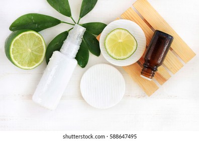 Natural cosmetics for home spa. Top view bottle of cream with water drops, essential oil, fresh lime fruit, green leaf decor, faded wooden background
