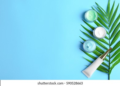Natural cosmetics and leaf on blue background