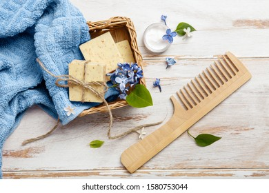 Natural cosmetics with lilac flowers for relax, spa and aromatherapy. Soap, cream, wooden comb and towel. Body care products. Prepare to bath. Organic cosmetic on wooden background with blue accents