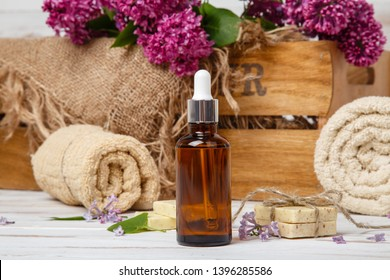 Natural cosmetics with lilac flowers. Serum or oil. Face care products. Prepare to bath. Spa therapy concept photo. Organic cosmetic on wooden background. Cosmetics for relax and aromatherapy