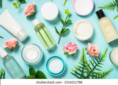 Natural cosmetics, Skin care product - cream, lotion, soap on blue background with green leaves and flowers. Flat lay image with copy space.