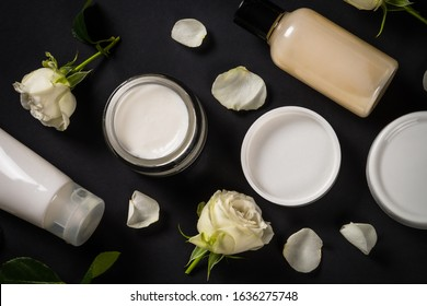 Natural cosmetics and Skin care product with rose oil on black. Cream, lotion, soap with rose flowers. Flat lay image with copy space.