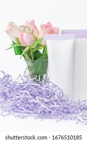 Natural cosmetics SPA mock-up on white background with flowers and soft paper filler. Organic cosmetic packaging cardboard box and plastic tube, night care cosmetic product concept, vertical