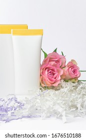 Natural cosmetics SPA mock-up on white background with flowers and soft paper filler. Organic cosmetic packaging cardboard box and plastic tube, Day care cosmetic product concept, vertical