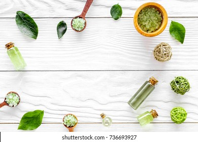 natural cosmetics with tea olive leaves and oil for homemade spa white wooden table background top view mock up