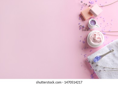 Natural cosmetics with towel and lavender on color background