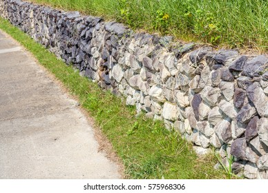 Natural countryside style of exterior stone cement wall beside entrance cement pathway, strong security concept.