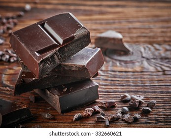 Natural dark chocolate pieces on wooden table