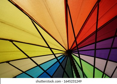 Natural daylight illuminates all the colors of the rainbow, shining through the colored umbrella surface. That creates an abstract view of a cheerful mood.