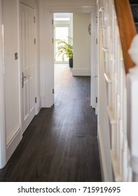 natural daylight illuminating the laminate wood flooring of a hall way in a residential home interior. The walls are white, the banister and stair case can be seen.