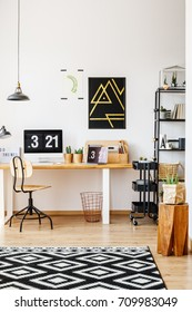 Natural decor of scandinavian study desk workspace with wooden furniture, retro chair, plants, lamps and computer with digital desktop clock