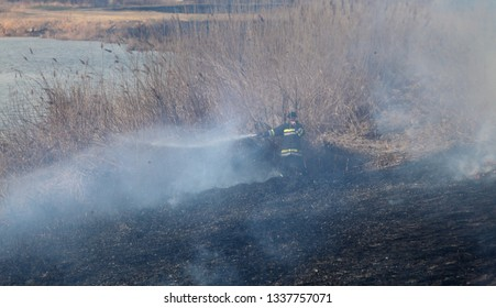 Natural disaster, firefighter extinguishes fire that destroying cane grass and bush at riverbank in marsh