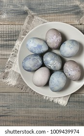 Natural dyed gray Easter eggs in plate with linen napkin on rustic grey wooden background. Top view point.