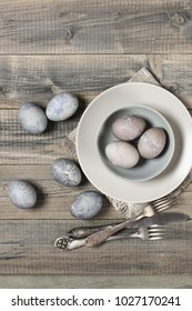 Natural dyed gray Easter eggs with plates and silverware on rustic grey wooden background. Top view point.
