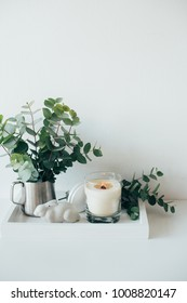 Natural eco home decor with green leaves and burning candle on t