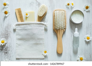 Natural eco and organic cosmetics products for hair care and facial treatment. Wooden hairbrush, essential oil, vegan soap, lotion and herbal mask with chamomile flowers. Top view on white background.