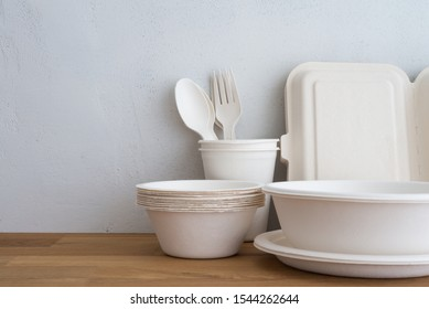 Natural eco-friendly disposable utensils (fork, spoon, dish plate, bowl, cup and fast food box container) made of fiber of bagasse and bamboo on wooden table with white wall background. Save the earth