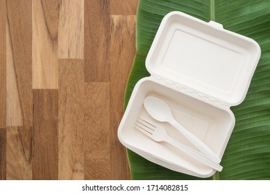 Natural eco-friendly disposable utensils (fork, spoon and fast food box container) made of fiber of bagasse and bamboo on green banana leaf and wooden table background with copy space. Save the earth.
