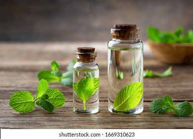 Natural essential oil and mint on a wooden background