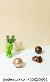 Natural evergreen fir branch in dented and crushed can on white table with brown and beige christmas baubles and gift. Beige background. Minimal Christmas or winter Holidays idea.