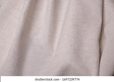 Natural fabric of gray beige, spread by waves.
