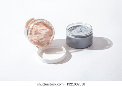 Natural face and body mask and Face and body Skin Scrub in containers on a light background with a shadow.